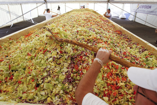 A volunteer mixes vegetables to create the world's biggest vegetable salad during a Guinness World Record attempt in Pantelimon, near Bucharest