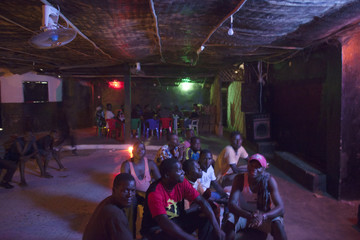 Young men watch television at a bar in Buba