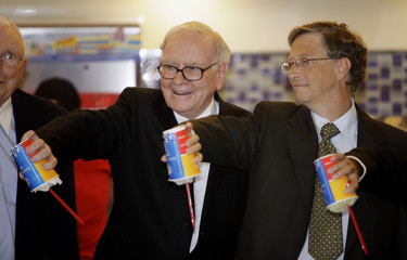 Billionaire financier and Berkshire Hathaway CEO Warren Buffett and Microsoft founder Bill Gates pose for a photo while each holding a cup of DQ ice cream upside down during their visit to a new Dairy Queen store in Beijing
