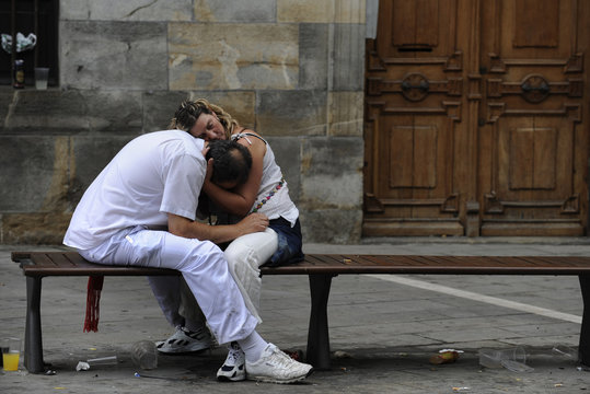 A sleeping couple embrace on the fifth day of the San Fermin festival in Pamplona.