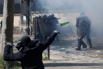 A hooded youth throws a bottle during a clash with French riot police to protest against the French labour law proposal during the May Day labour union march in Paris