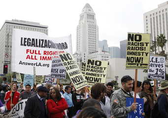 Demonstrators walk with signs as Los Angeles City Hall is seen in the background during an Occupy ICE protest march in Los Angeles