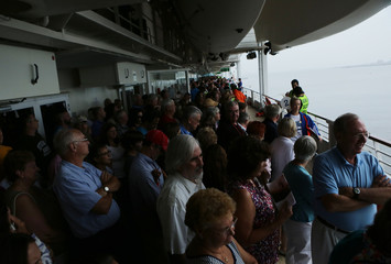 Tourists muster to their lifeboat stations during practice drills aboard the Royal Caribbean cruise ship Grandeur of the Seas