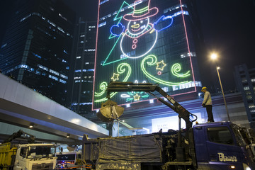 A crane removes tents and wood under Christmas lights near the government headquarters building at the financial Central district in Hong Kong