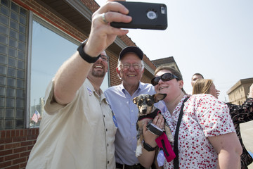 Sen. Bernie Sanders takes a photo with Seth and Mandy Farrow during the Independence Day Parade in Creston, Iowa