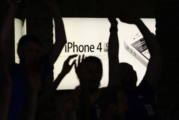 Apple employees celebrate as they open the doors to customers in Covent Garden, London