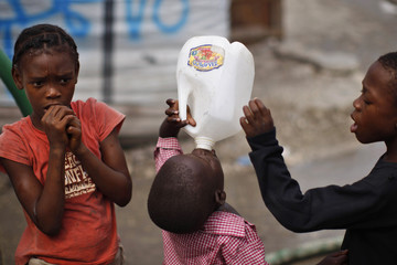 An earthquake survivor drinks water from a container in a provisional camp in downtown Port-au-Prince