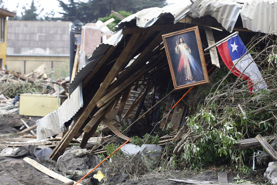 A Chilean flag and a religious icon hang from debris left by waves generated by a major earthquake in Iloca