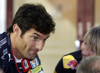 Red Bull Formula One driver Mark Webber of Australia reacts in the paddock ahead of the third practice session of the Singapore F1 Grand Prix at the Marina Bay circuit