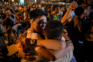 Activists hug each other after it was announced that the execution was delayed for Veloso, during a vigil outside Indonesian embassy in Makati