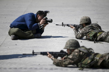 A photographer takes pictures of South Korean army soldiers taking part in a U.S.-South Korea joint live-fire military exercise at a training field in Pocheon