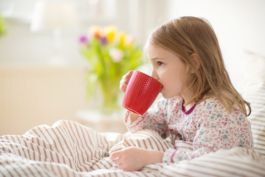 Pretty sick little child girl laying in bed drink tea