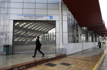 A woman walks in front of a closed metro station during a 24-hour strike against the government's austerity measures in Athens