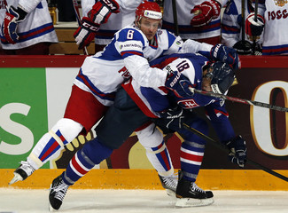 Russia's Denisov fights for the puck with Slovakia's Satan during their 2013 IIHF Ice Hockey World Championship preliminary round match at the Hartwall Arena in Helsinki