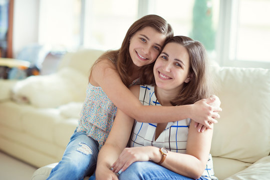Portrait of pretty young mother with her tennager daughter