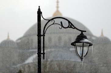 Icicles hang from a street light with the dom of the Sultanahmet mosque, known as the Blue mosque, seen in the background, in Istanbul