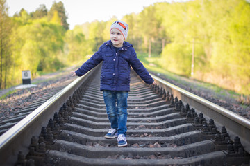 A small pre-school boy plays on the railway without supervision from adults. Railway - a zone of increased danger