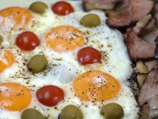 fried eggs with bacon, olives and tomatoes a hearty breakfast.