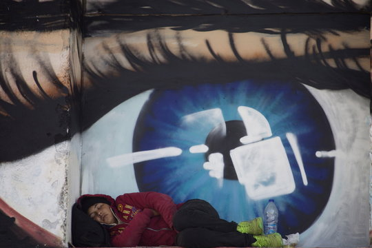 Refugees and migrants sleep in front of a graffiti covered wall depicting a human eye at the port of the city of Mytilene on the island of Lesbos