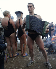 A man plays an accordion as winter swimmers gather round a fire after bathing in the icy waters of a pond at the Victory Park, with the air temperature at about minus 15 degrees Celsius in St. Petersburg