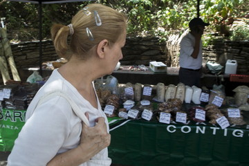 A woman looks at goods at a street market in Caracas