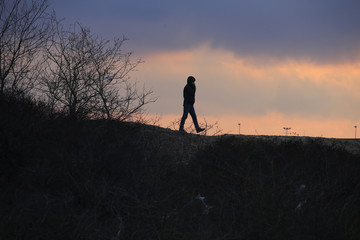 """A migrant walks on top of a pile of sand which separates the road that leads to the ferry terminal and the camp known as the """"Jungle"""", a squalid, sprawling camp in Calais"""