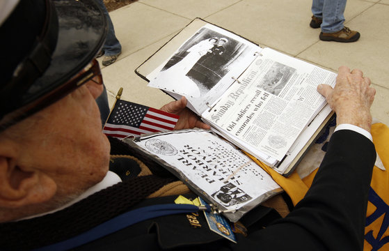 Veteran Edward Borucki from Massachussetts flips through his scrapbook during a ceremony honoring those who served in the Pacific theater at the WWII Memorial in Washington