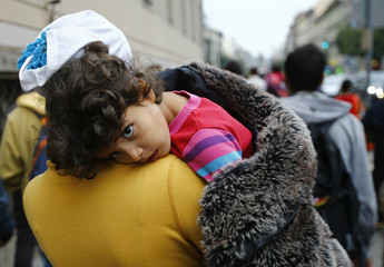 Migrant women holds her child as she walks down street from Keleti train station in Budapest
