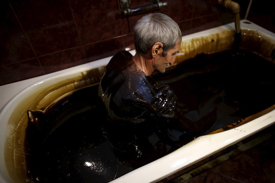 A man smears crude oil on his body as he lies in a bathtub during a health therapy session at Naftalan Health Center in Baku
