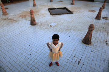 A girl poses for a picture as she plays near fountains that are switched off at Lalbagh Kella in old Dhaka