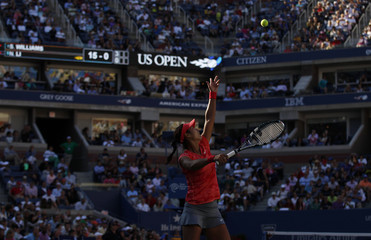 Li Na of China serves to Serena Williams of the U.S. at the U.S. Open tennis championships in New York