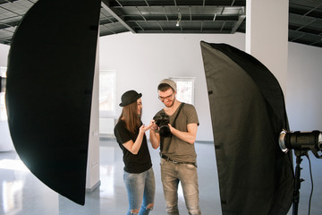 Model and photographer enjoy photos on camera. Man with camera show pictures to happy casual woman during the studio session.