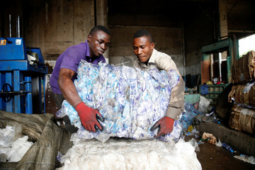 Men lift compressed waste from a machine at the Wecycler waste recycling centre in Ebutte Metta district in Lagos