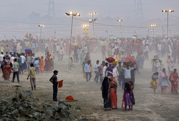 Vendor selling garlands waits for customers as Hindu devotees gather to worship the Sun god Surya on the banks of the river Yamuna during the Hindu religious festival of Chatt Puja in New Delhi