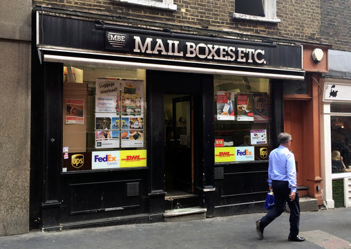 A man walks past a branch of Mail Boxes Etc. in London