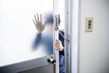 ドアを無理やり開けようとする男性