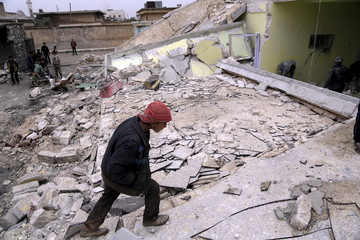 A boy inspects his school, damaged in what activists said was an air strike carried out yesterday by the Russian air force in Injara town, Aleppo countryside, Syria