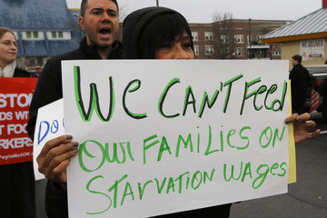 Gladys Jimenez holds a sign during a demonstration in support of higher minimum wages for fast food and other workers in Boston