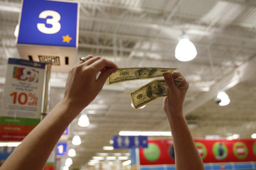A cashier holds hundred dollar bills up to the light at the register of a Toys R Us store on the Thanksgiving Day holiday in Manchester