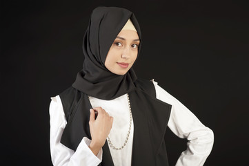 Portrait of a beautiful Muslim woman in modern oriental clothes on an isolated black background