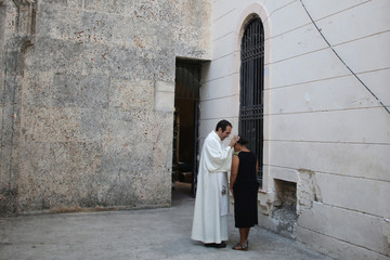 A member of the Catholic Church blesses a believer before a mass at the Havana's Cathedral, Cuba