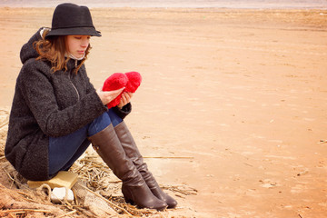 A young woman in a hat and coat sits on the shore of the bay on a fishing net with a plush heart in her hands