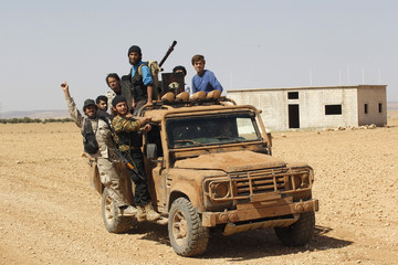 Free Syrian Army fighters react to the camera as they ride in a vehicle mounted with a weapon in the Hama countryside
