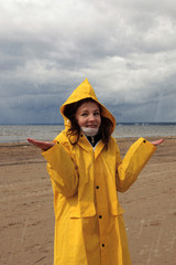 A young girl in a yellow raincoat is standing in the rain on the shore of the bay, dark clouds with rain, hands raised, early spring, bad weather, good mood
