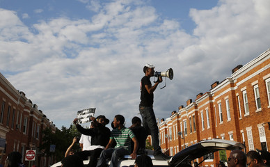 A man with a bullhorn addresses a large crowd at a rally in Baltimore