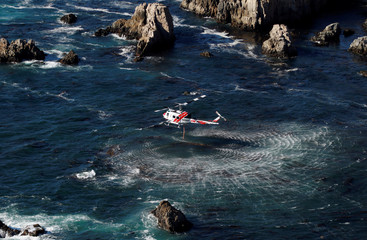 A Cal Fire helicopter picks up water from the Pacific Ocean at Garrapata State Park during the Soberanes Fire north of Big Sur
