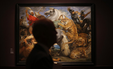 "A visitor is silhouetted near ""Tiger, Lion and Leopard Hunt"" from 1617 by Peter Paul Rubens at an exhibition in London"