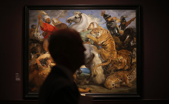 """A visitor is silhouetted near """"Tiger, Lion and Leopard Hunt"""" from 1617 by Peter Paul Rubens at an exhibition in London"""