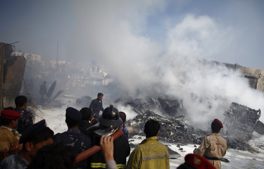 Army and police officers examine the wreckage of a plane after it crashed in Sanaa