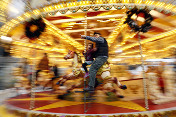 People ride a merry-go-round outside the Natural History Museum in London